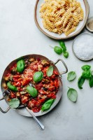 a pan with roasted tomato eggplant sauce with a bowl of pasta, a bowl of salt, and basil leaves