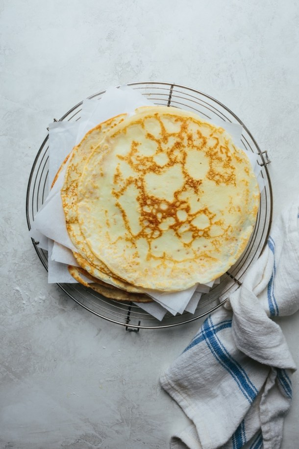a stack of cooked crepes layered with parchment papers