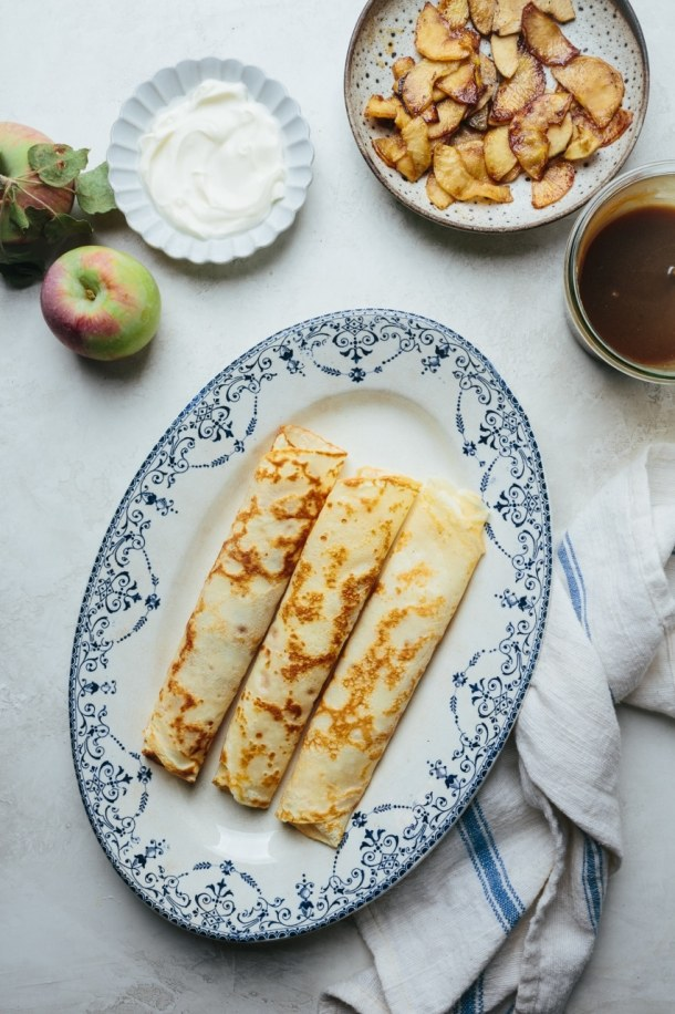 a plate of crepes with two apples, a plate of creme fraiche, a bowl of sauteed apples, and a jar of salted caramel