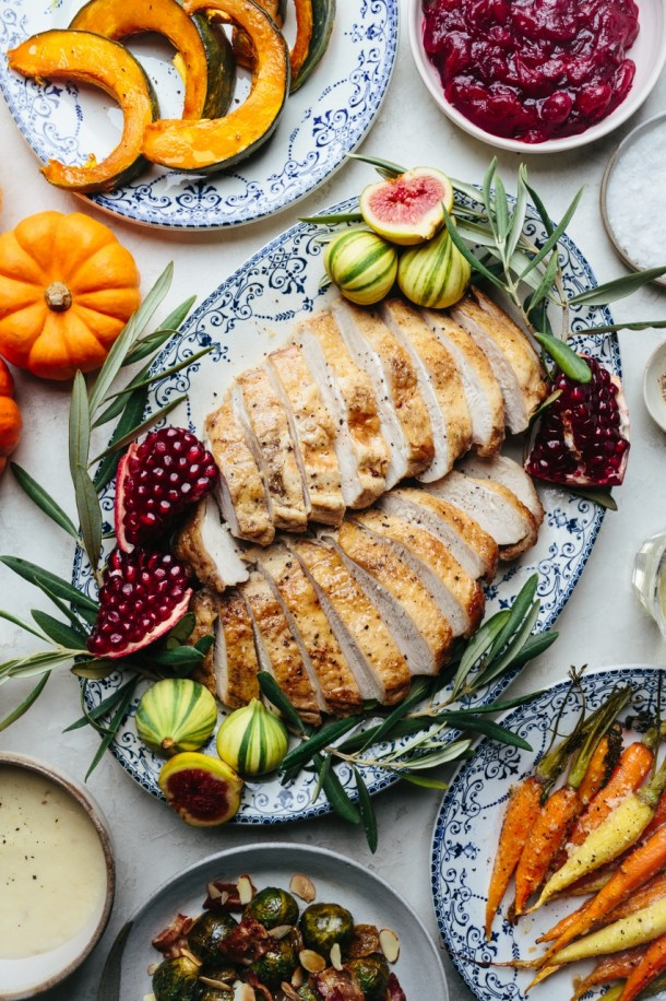 platter of sliced turkey breasts with sides of roasted squash, roasted carrots, roasted brussels sprouts, cranberry sauce, gravy, decorative pumpkins, and wine glasses