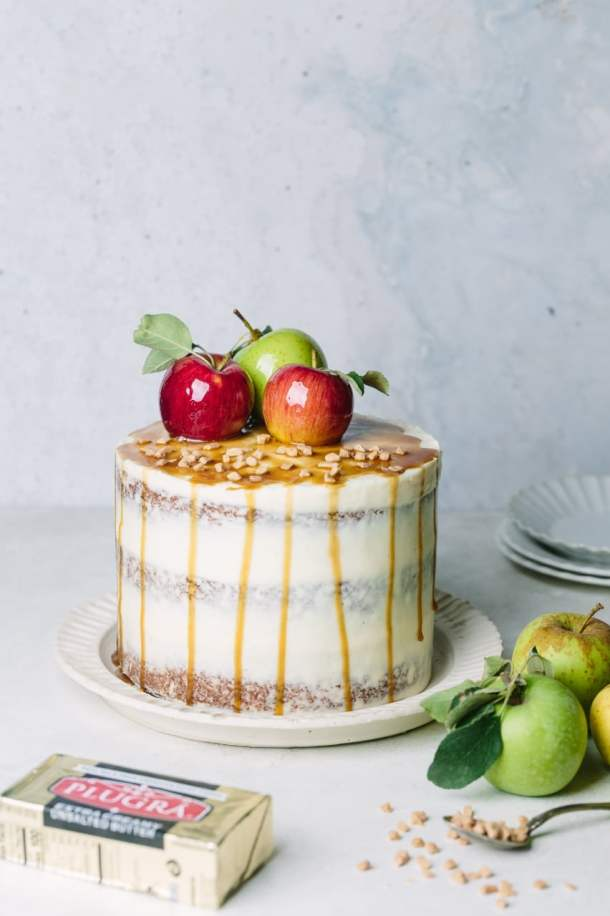 toffee apple cake next to fresh apples, a spoon with toffee pieces, block of butter, and serving plates