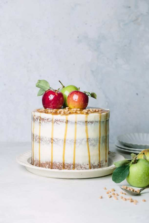 toffee apple cake next to fresh apples, a spoon with toffee pieces, and serving plates