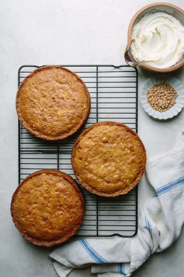 three baked cakes on top of a cooling rack next to a kitchen towel, a bowl of frosting, and a plate of toffee