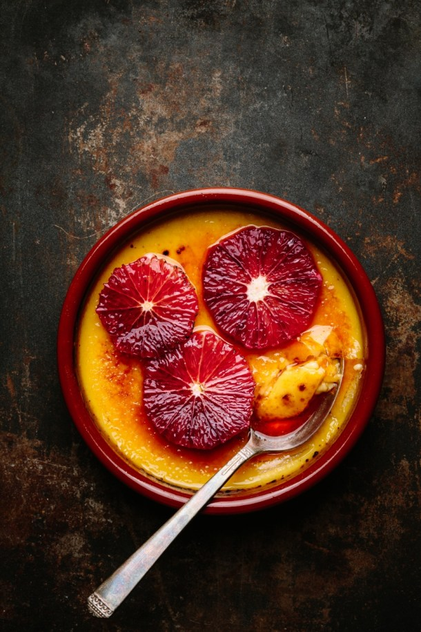 creme brulee topped with blood orange slices in ramekin with spoon