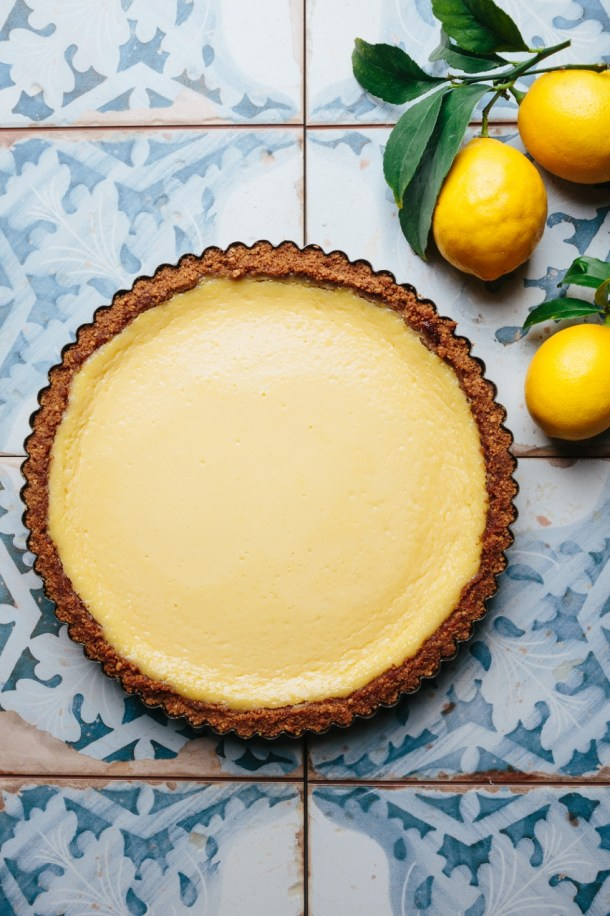 a baked lemon meringue tart next to three lemons