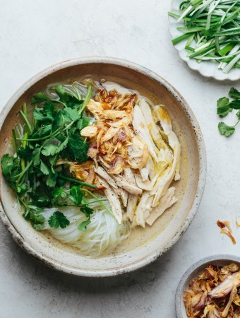 a bowl of chicken glass noodle soup next to a plate of scallions and a bowl of fried shallots