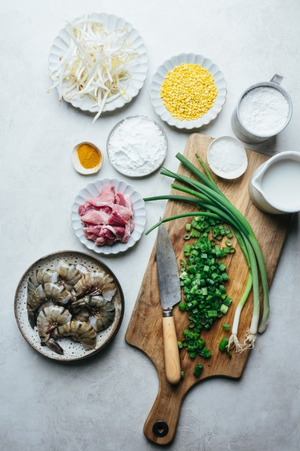 ingredients for crepes: scallion on chopping board with knife, plate of prawns, plate of sliced pork, plate of turmeric, bowl of cornstarch, plate of mung bean, plate of bean sprouts, bowl of salt, cup of rice flour, and cup of coconut cream