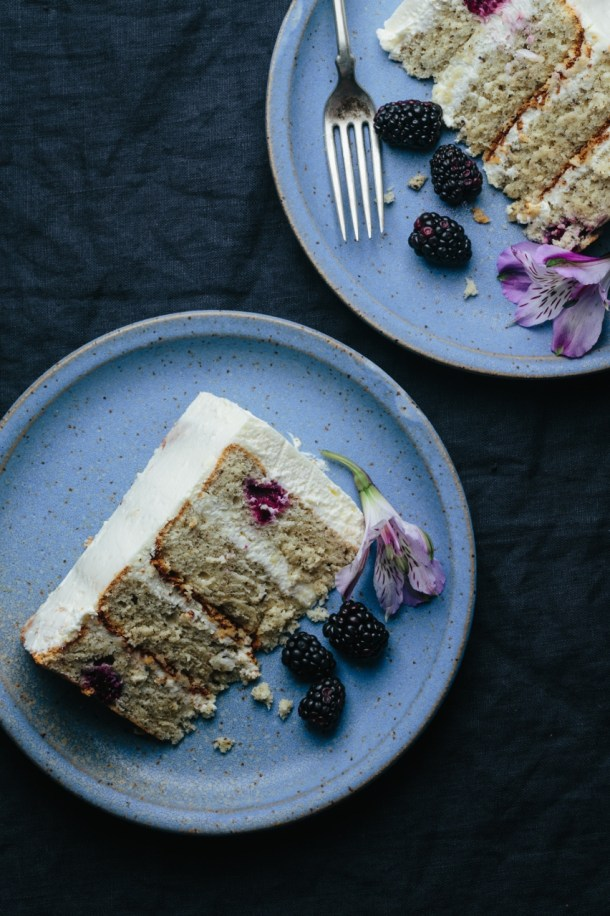 two slices of blackberry Earl Grey cake on serving plates with fresh blackberries and flowers