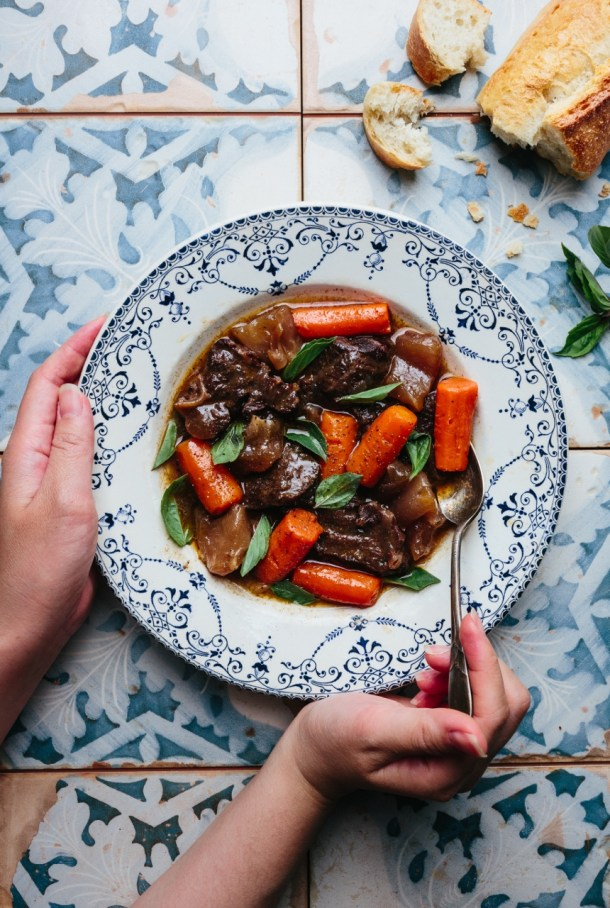 hand hold a spoon and another hand hold the bowl of beef stew next to pieces of baguette