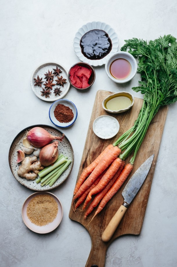 ingredients for beef stew: carrots on a chopping board with a knife along with a bowl of salt and a bowl of oil, plate of sugar, plate of lemongrass, shallot, and ginger, a bowl of Chinese five spice, a bowl of star anise, a bowl of tomato paste, a plate of Hoisin sauce, a bowl of fish sauce