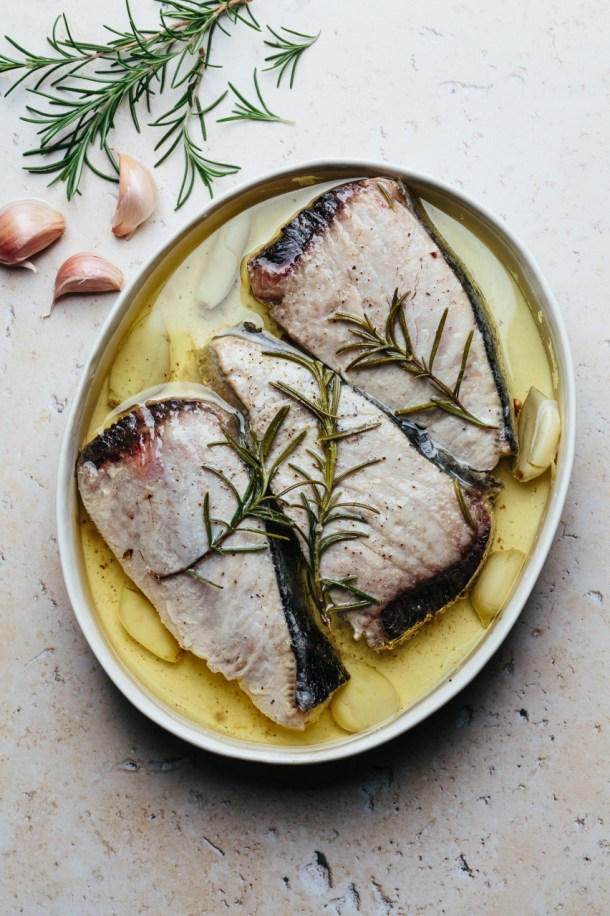 tuna confit in a baking dish with olive oil, garlic, and rosemary next to three cloves of garlic and fresh rosemary