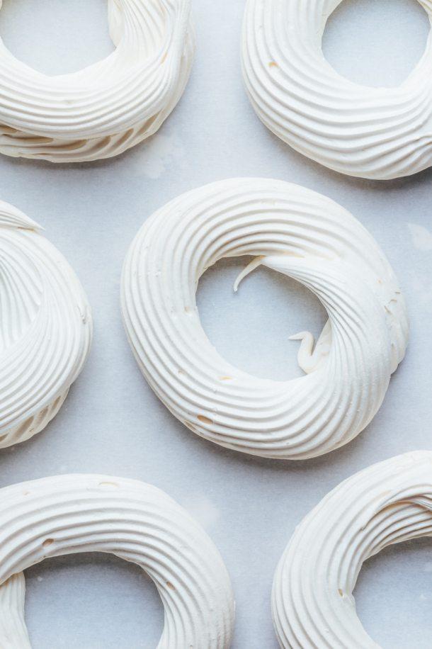 baked pavlova nests on lined baking sheet