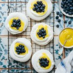 Swiss meringue pavlova nests on a cooling rack next to a bowl of whipped cream, plate of blueberries with scattered blueberries, bowl of lemon curd and kitchen linen