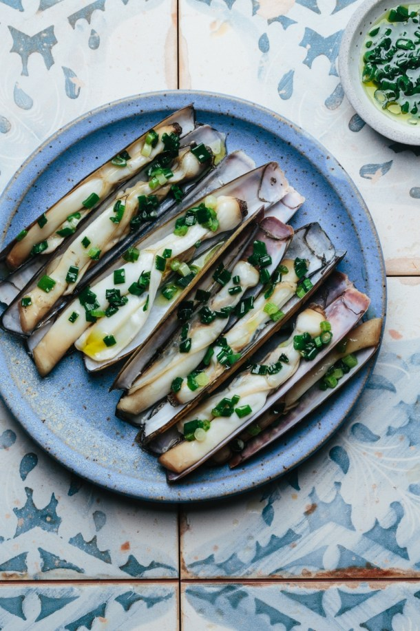 a plate of grilled razor clams topped with scallion oil next to a bowl of scallion oil