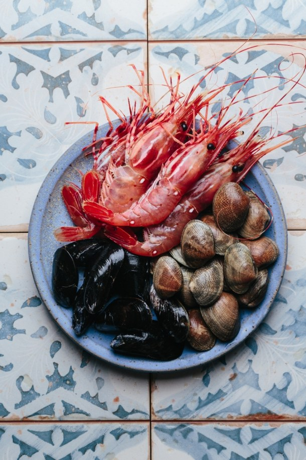 a plate containing spot prawns, mussels, and clams