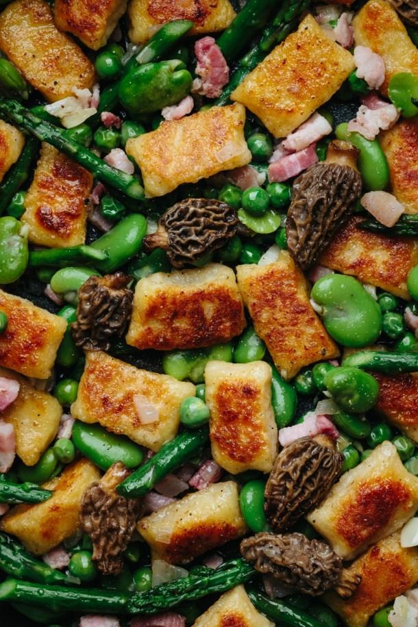 close up of gnudi with fava, peas, asparagus, morel mushrooms, and pancetta