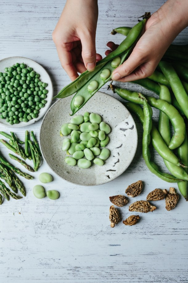 hands podding fava beans next to a bowl of shelled fava, unshelled fava, a plate of peas, cut asparagus, and morel mushrooms