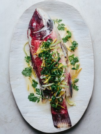 a plate of steamed fish with ginger and scallions