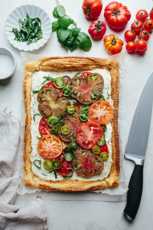 tomato tart next to next to fresh tomatoes, basil leaves, a bowl of salt, and a knife