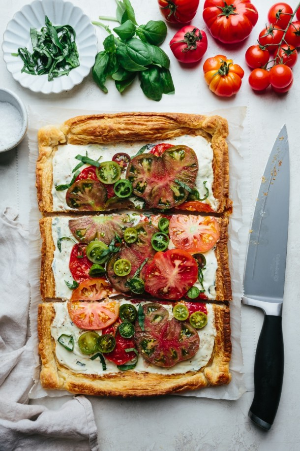 cut tomato tart next to next to fresh tomatoes, basil leaves, a bowl of salt, and a knife