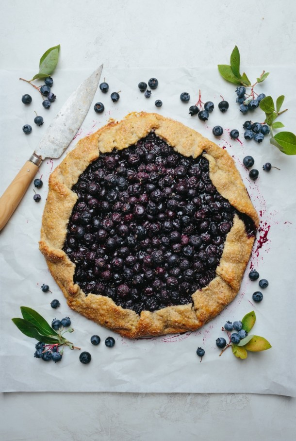 a baked galette next to a knife and fresh blueberries