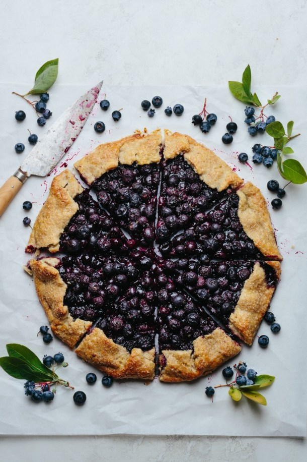 a galette sliced into 8 pieces next to a knife and fresh blueberries