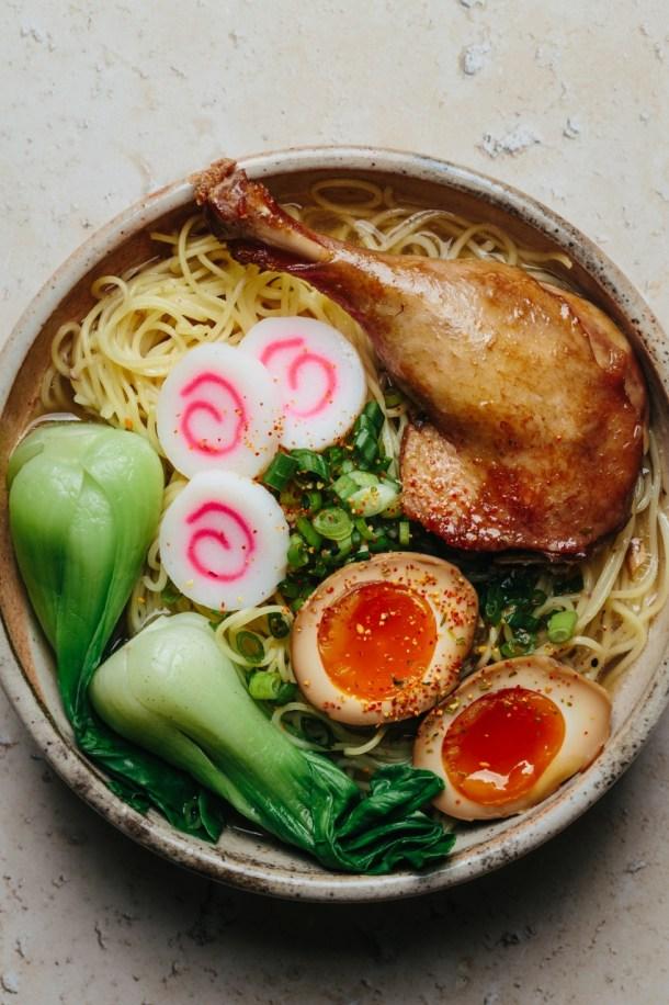 a ramen bowl containing noodles, soup, duck leg, fish cake, soy sauce eggs, and bok choy