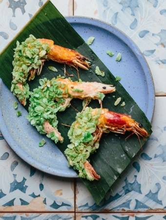 a plate with three green rice flake crusted prawns on a plate lined with banana leaf