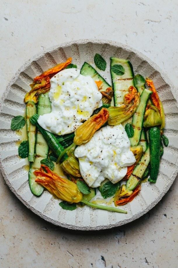 a close up of a plate of grilled zucchini and zucchini blossoms with mozzarella di bufala
