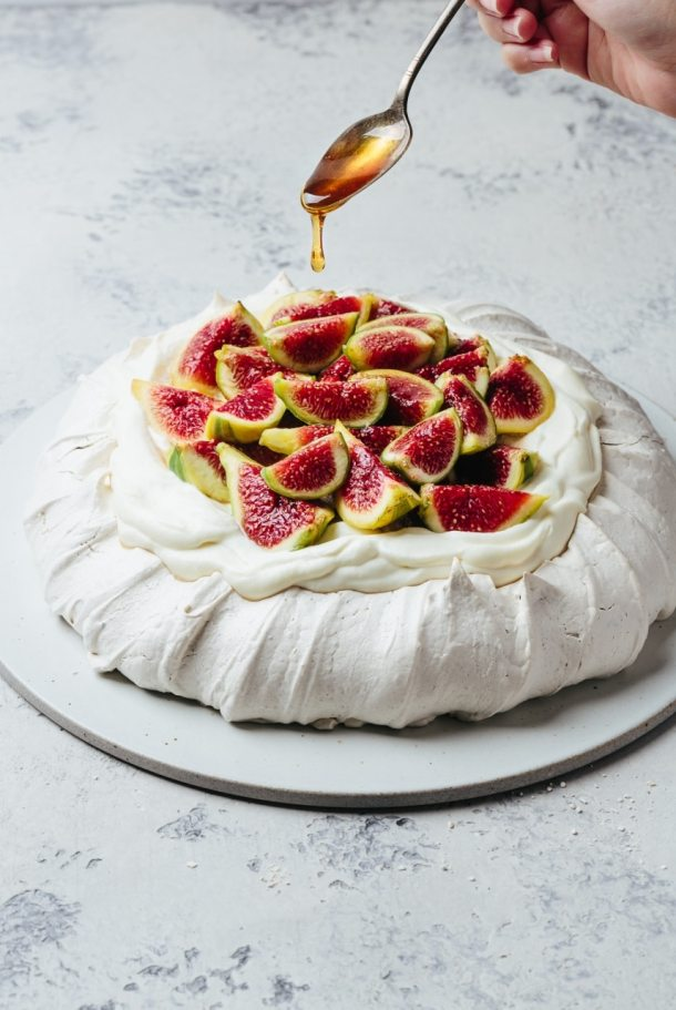 hand holding spoon drizzling syrup onto pavlova