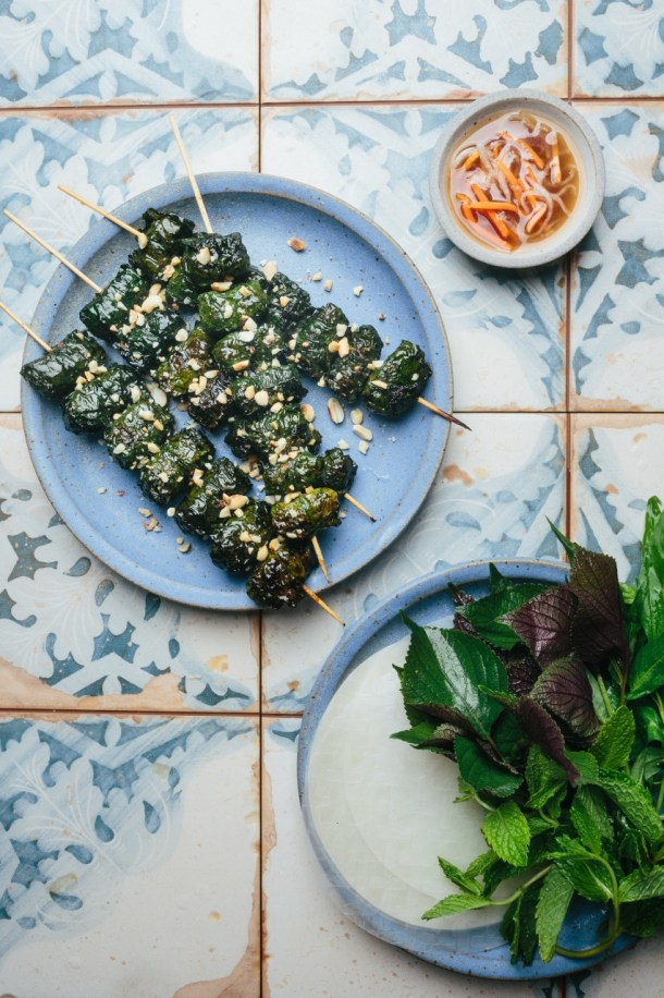 a plate with four skewers of grilled beef wrapped in betel leaves next to a bowl of dipping sauce and a plate with rice paper and Vietnamese herbs