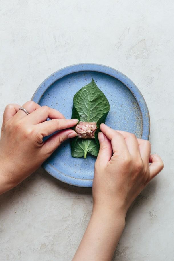 hands folding two sides of betel leaf over filling