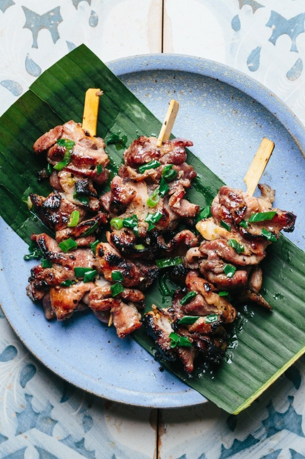 a plate with three skewers of grilled pork over a piece of banana leaf
