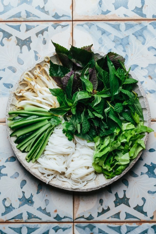 a bowl containing vermicelli noodles, cucumber, bean sprouts, Vietnamese herbs, and lettuce