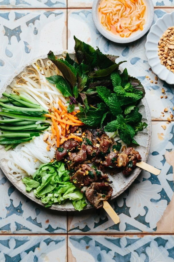 a bowl containing grilled pork skewers, vermicelli noodles, cucumber, bean sprouts, Vietnamese herbs, lettuce, pickled vegetables, roasted peanuts and dipping sauce next to a bowl of dipping sauce with pickled vegetables and a bowl of roasted peanuts