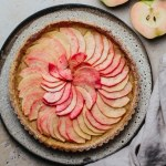 pink pearl apple tart on a platter next to a linen and fresh apples