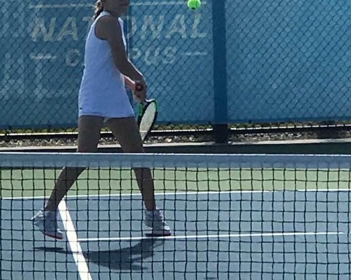 girl on tennis court hitting backhand