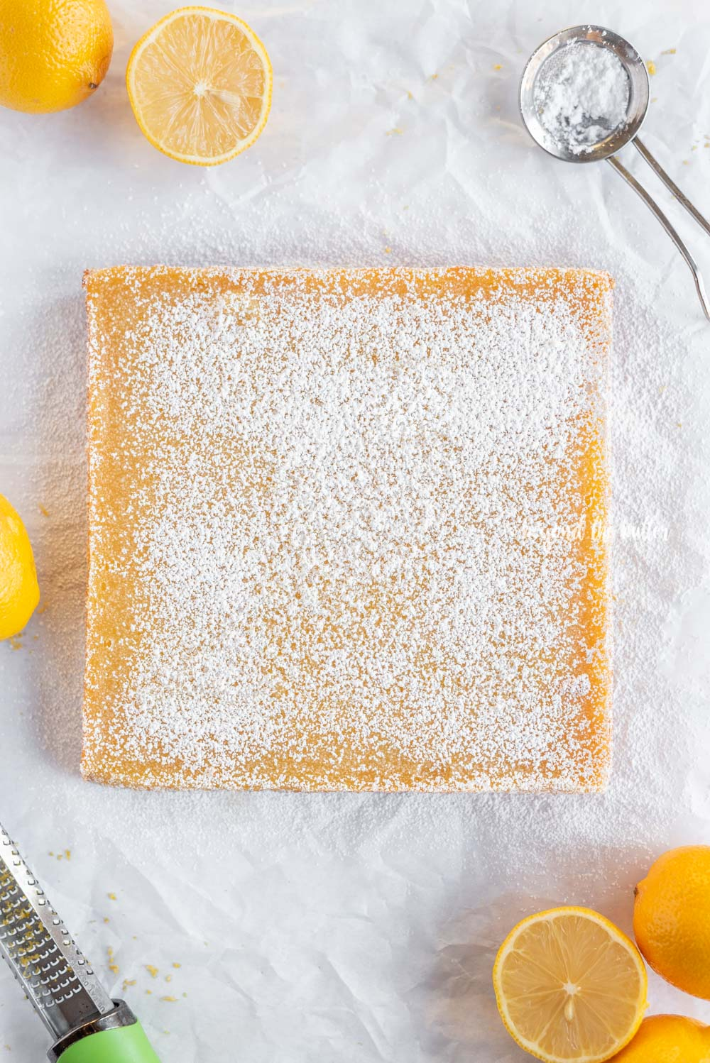 Overhead image super easy lemon bars dusted with confectioners sugar   All Images © Beyond the Butter, LLC