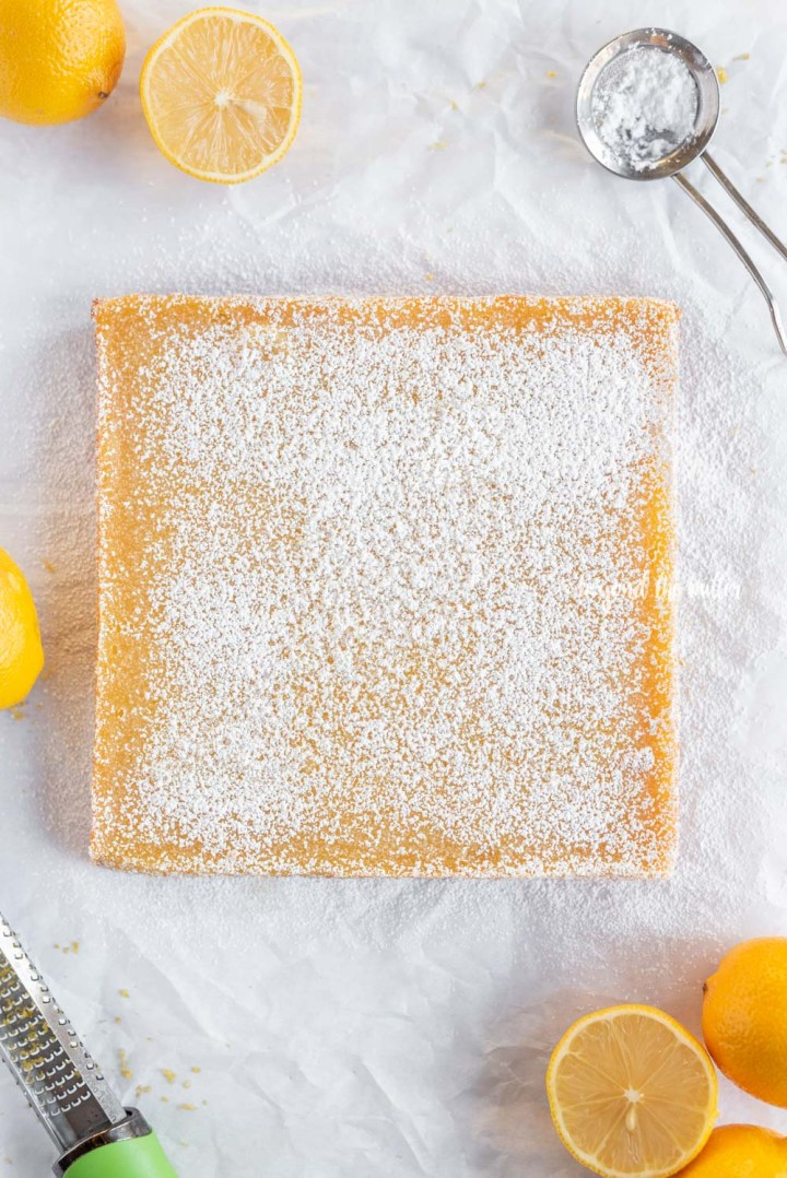Overhead image super easy lemon bars dusted with confectioners sugar | All Images © Beyond the Butter, LLC
