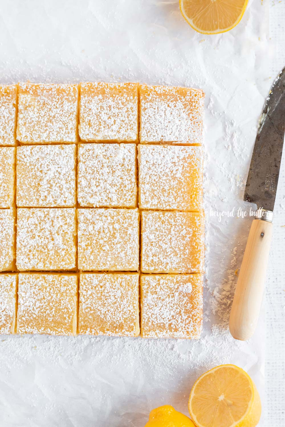 Overhead image of just sliced lemon bars with knife | All Images © Beyond the Butter, LLC