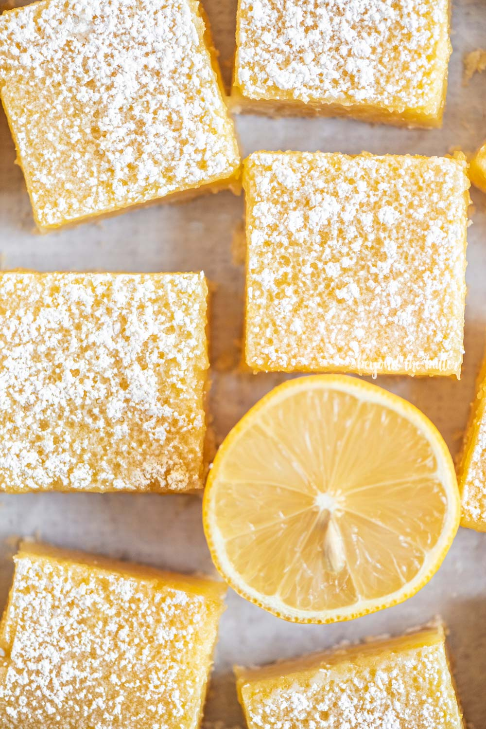 Overhead closeup image of super easy lemon bars with half cut lemon | All Images © Beyond the Butter, LLC
