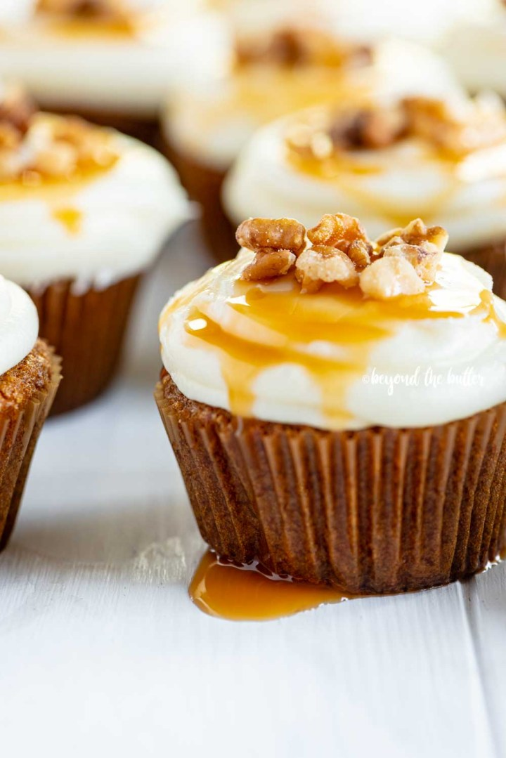 Angled image of super moist carrot cake cupcakes with caramel and walnuts on top | All Images © Beyond the Butter™