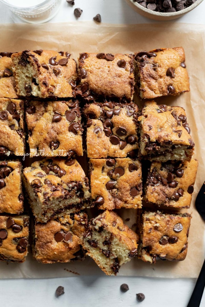 Cut squares of chocolate chip sour cream coffee cake on brown parchment paper with bowl of chocolate chips | © Beyond the Butter®