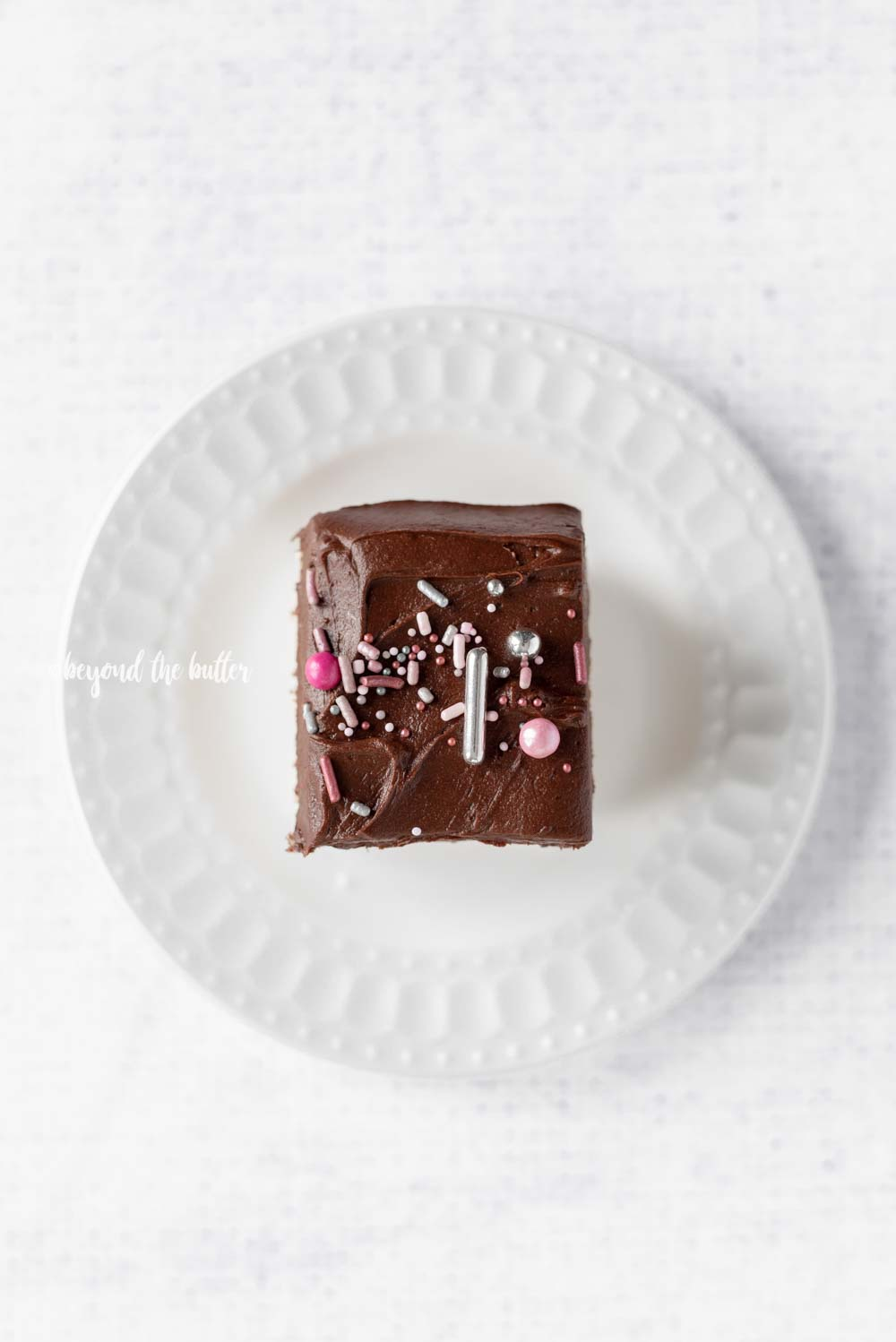 Single slice of Classic 4 Egg Yellow Sheet Cake with Chocolate Frosting and sprinkles on a dessert plate | All Images © Beyond the Butter, LLC