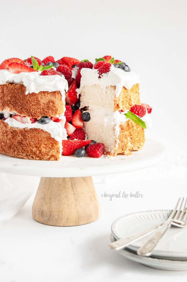 Angel Food Cake with Berries | Angel Food Cake on a cake stand that has a few slices taken out | Image and Copyright Policy: © Beyond the Butter, LLC