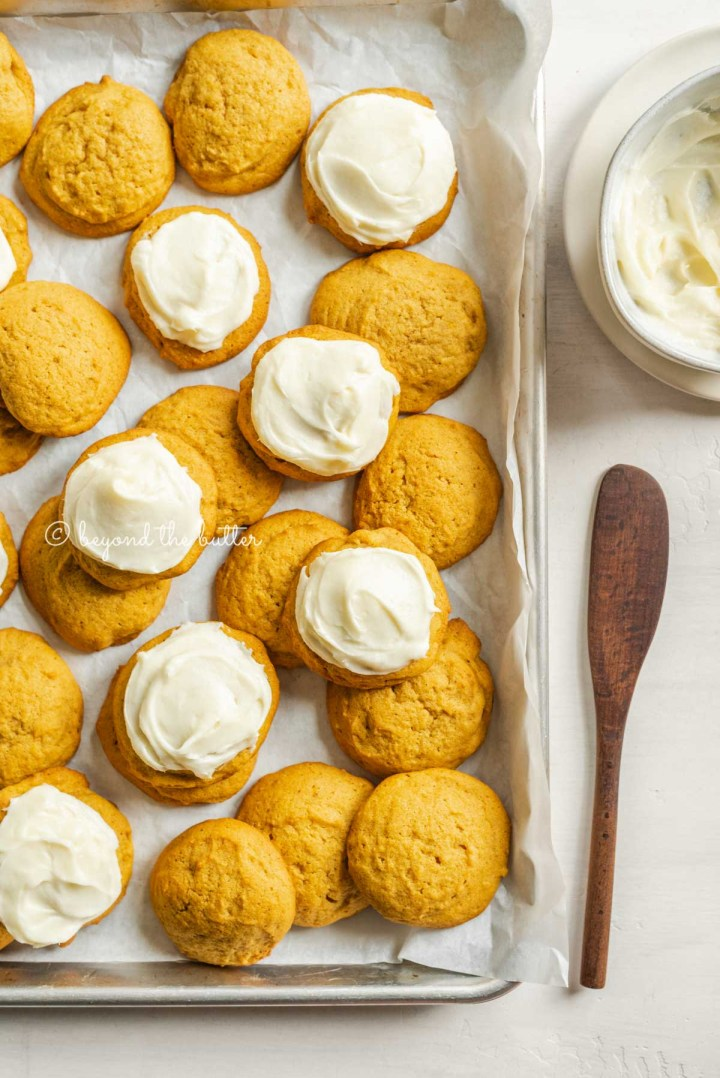Parchment paper lined baking sheet with partially frosted pumpkin cinnamon cookies with bowl of cream cheese frosting and spreader to the right | All Images © Beyond the Butter™