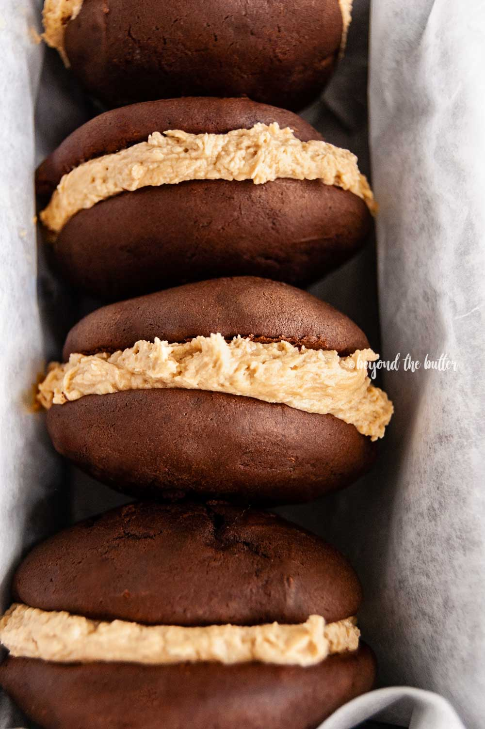 Closeup overhead image of chocolate peanut butter whoopie pies stacked in a parchment lined baking pan | All images © Beyond the Butter™