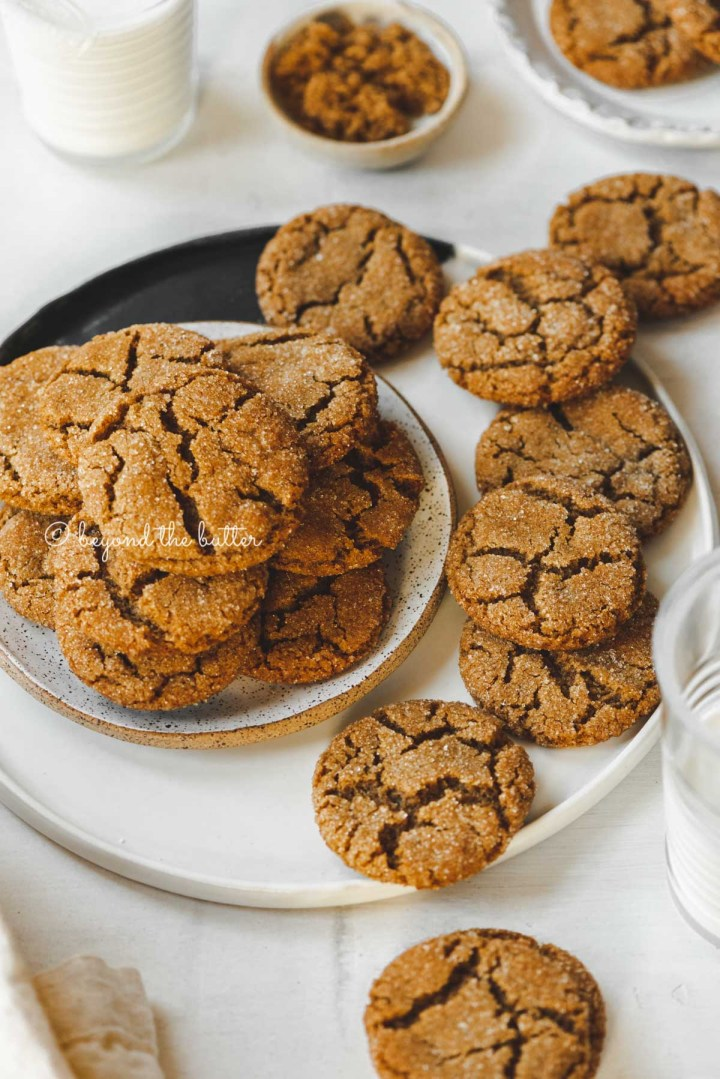 Small plate of molasses cookies placed on a larger plate filled with soft molasses cookies and one that is half eaten | All Images © Beyond the Butter™