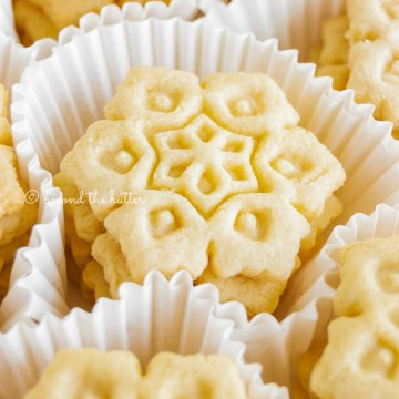 White treat liners filled with stacked homemade butter cookies | All Images © Beyond the Butter™