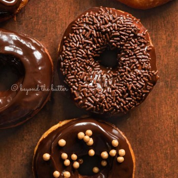 Chocolate glazed decorated donuts on dark wood background | All Images © Beyond the Butter™